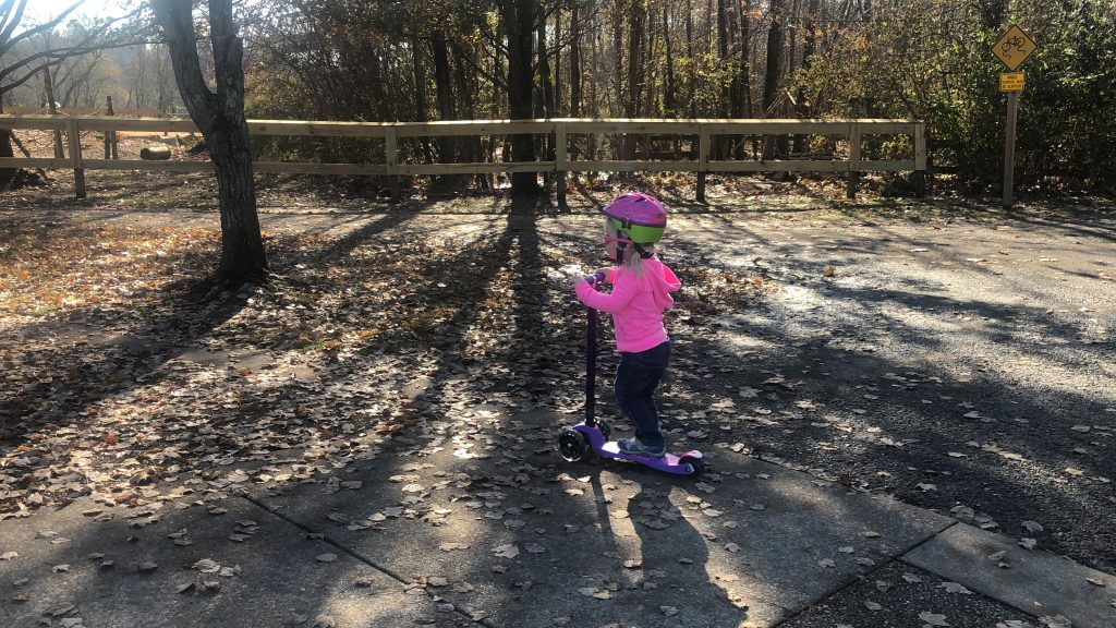 small girl on a purple scooter at a park